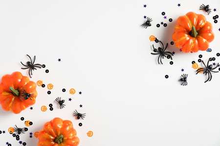 Happy halloween holiday concept. Flat lay composition with pumpkins, spiders, confetti on white desk. Halloween background, party invitation card, banner mockup. Top view. Foto de archivo