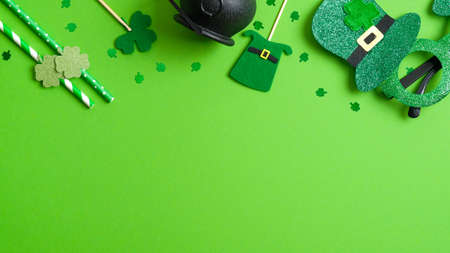 St Patrick's day top frame border of shamrock four leaf clover, pot of gold, Patricks Day glasses, felt hat, drinking straws on green background. Patricks day party invitation template, greeting card