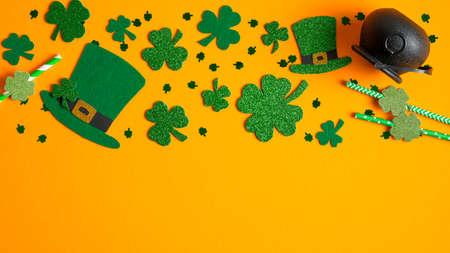 St Patricks Day frame border of shamrock and four-leaf clovers, Irish elf hats, pot of gold on orange background. Banner design, greeting card mockup. Happy St Patrick's Day concept