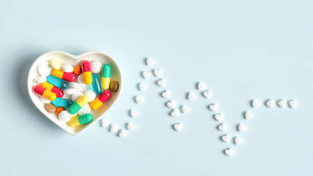 Heartbeat line made of heart shaped pills and bowl with colorful medical tablets. Heartbeats cardiogram. Heart health concept