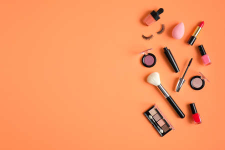 Makeup cosmetics and beauty products spilling out on pastel peach colored background. Flat lay, top view. Beauty salon banner design template