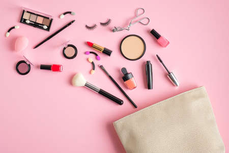 Cosmetics bag with makeup products spilling out on pastel pink background. Flat lay, top view
