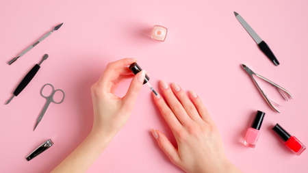 Woman making manicure herself. Female hands with nail polish and manicure tools on pink background, view from above. Self-care beauty treatment concept