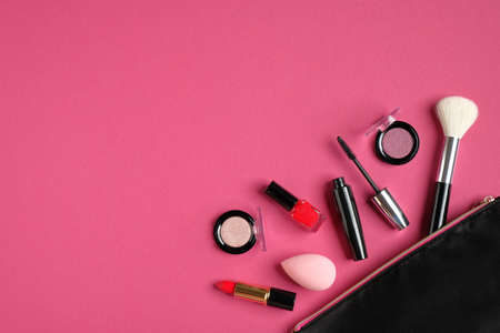 Make up bag and decorative cosmetics on pink background. Flat lay, top view. Beauty and fashion concept.