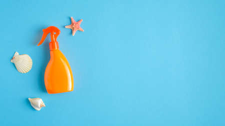 Orange sunscreen spray bottle and seashell on blue background. Sun protection on summer vacation concept