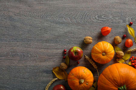 Thanksgiving or harvest background. Pumpkins, walnuts, dry leaves, apple on rustic wooden table. Flat lay, top view, copy space.