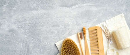 Set of personal hygiene accessories on stone background. Zero waste, plastic free SPA bath products. Flat lay, top view towel with body brush, bamboo toothbrushes, hair comb, ear sticks, loofah sponge