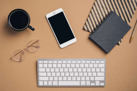 Top view, flat lay keyboard, cup of coffee, paper notebooks, glasses on office desk. Elegant feminine workspace. Business concept