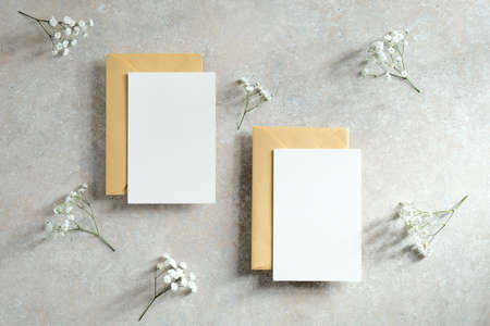 Wedding invitation cards mockup design. Blank paper cards, envelopes, gypsophila flowers on stone table. Flat lay, top view.