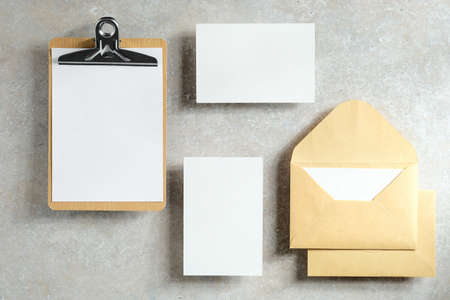 Wedding stationery set on stone table top view. Flat lay blank paper cards, clipboard, envelopes.