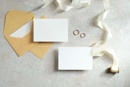 Blank paper cards with envelope, ribbon and golden rings on stone table. Flat lay, top view. Wedding invitation card mockup design.
