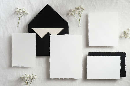 Elegant wedding stationery top view. Flat lay blank paper card, envelopes, flowers on white background.