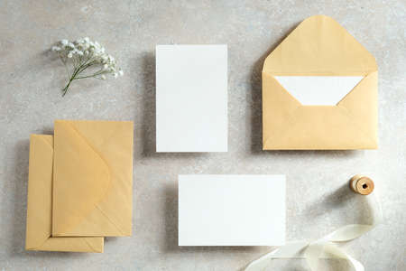 Wedding invites and stationery top view. Blank paper cards mockups, kraft paper envelopes, ribbon, flowers on stone table. Vintage style. Flat lay.