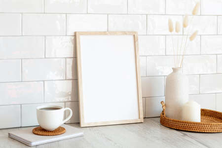 White picture frame mockup and home decor on table. Scandinavian living room interior design. Nordic style.