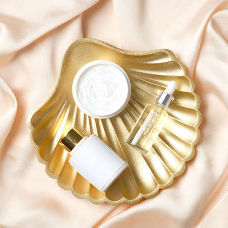 Golden pearl shell decoration with set of cosmetics products. Flat lay, top view.