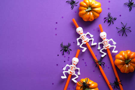 Happy Halloween party composition with pumpkins, drinking straws with skeletons, spiders, bats on purple background. Flat lay, top view. Standard-Bild