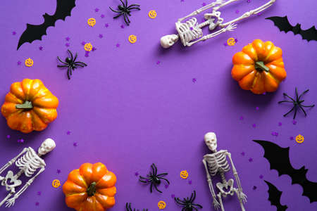 Happy Halloween holiday party composition with pumpkins, skeletons, spiders, bats, confetti on purple background. Top view, flat lay.