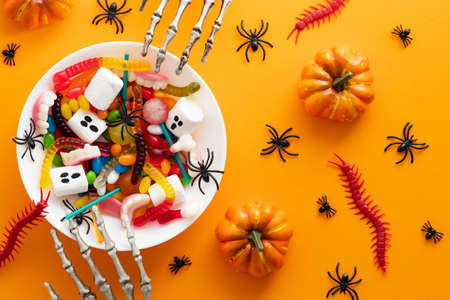 Halloween sweets in plate and decorations on orange background. Happy halloween holiday concept. Flat lay, top view, overhead.