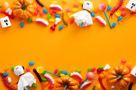 Happy Halloween holiday banner design. Frame border made of halloween decorations and candies on orange background. Flat lay, top view, copy space.
