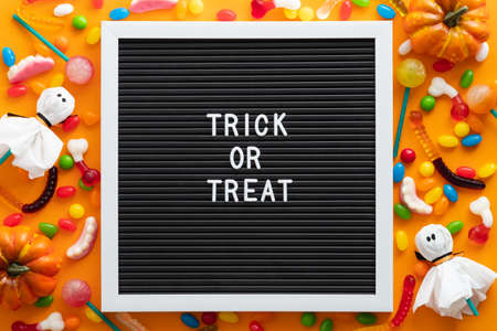 Trick or treat letter board with colorful Halloween candies and decorations on orange background. Flat lay, top view, overhead. Happy Halloween concept.