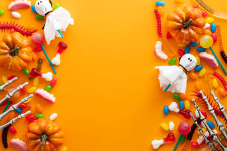 Happy Halloween holiday banner mockup. Frame made of halloween decorations and candies on orange background. Flat lay, top view, copy space.