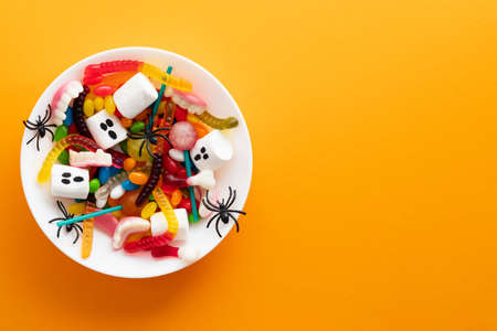 Halloween sweets and decorations in plate on orange background. Happy Halloween holiday concept. Flat lay, top view, copy space. Standard-Bild
