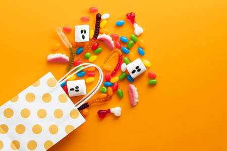Happy Halloween holiday sale. Shopping bag with sweets on orange background. Flat lay, top view, overhead.
