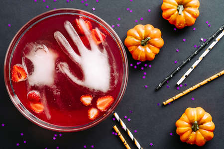 Halloween party beverage with frozen hands on black background. Flat lay, top view.