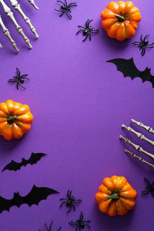 Halloween poster with festive decorations, pumpkins, spiders, skeletons hands, bats on purple background. Flat lay, top view, overhead. Standard-Bild