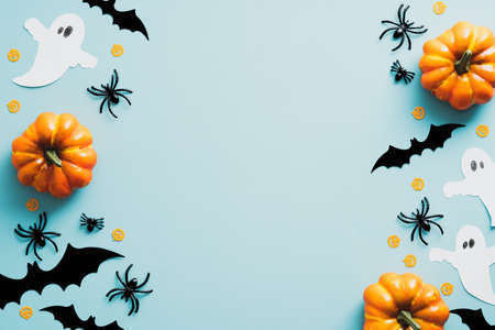 Halloween flat lay composition with orange pumpkins, ghosts, spiders, bats on blue background. Happy Halloween holiday greeting card mockup. Flat lay, top view, copy space. Standard-Bild