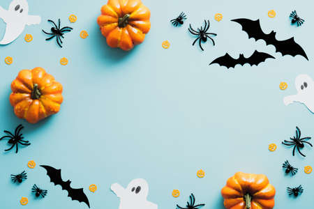 Happy halloween holiday concept. Halloween decorations, bats, ghosts, spiders, pumpkins on blue background. Halloween party greeting card mockup with copy space. Flat lay, top view, overhead.