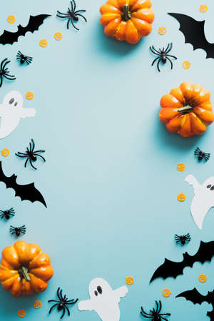 Happy halloween holiday concept. Halloween decorations, bats, ghosts, spiders, pumpkins on blue background. Halloween party poster mockup with copy space. Flat lay, top view, overhead. Standard-Bild