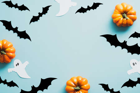 Halloween flat lay composition with bats, ghosts, pumpkins on blue background. Vintage style. Happy Halloween holiday concept.