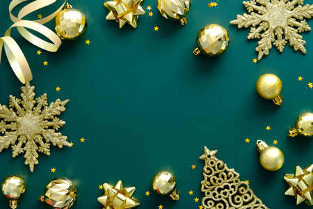 Bright Christmas background with golden decorations on green table. Flat lay, top view golden snowflakes, balls, ribbon. Happy New Year greeting card template, Luxury Xmas banner design.