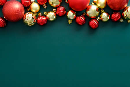 Merry Christmas banner design. Flat lay red and golden balls decorations on green background. Vintage style. Flat lay, top view, overhead. Standard-Bild