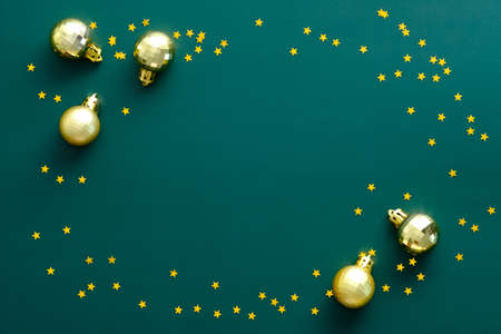 Vintage Christmas frame made of golden balls and confetti stars on green background. Flat lay, top view, overhead.