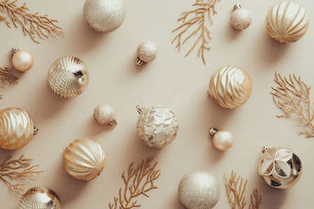 Christmas flat lay composition with golden balls and Xmas tree branches on beige background. Flat lay, top view. Standard-Bild