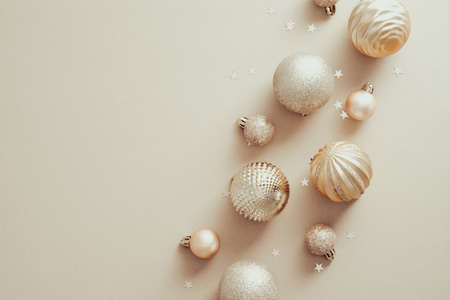 Christmas and New Year holidays concept with golden balls decorations on pastel beige background. Top view, flat lay. Minimal style.