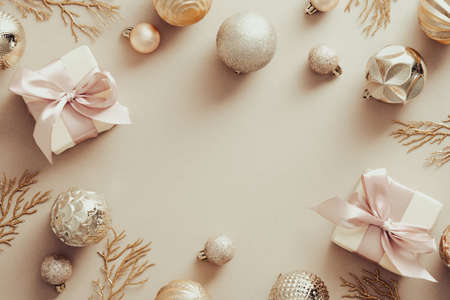 Christmas frame made of balls, gift boxes, Xmas tree branches on pastel begieg background. Top view. Flat lay. Standard-Bild