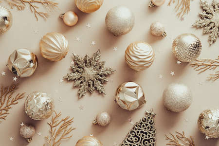 Elegant Christmas decorations on pastel beige background, flat lay. Merry Christmas and Happy New Year concept.