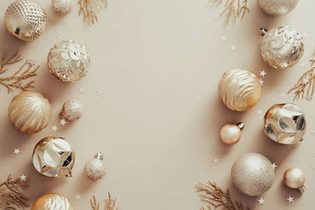 Christmas composition. Frame made of golden balls decorations on pastel beige background. Christmas, winter, new year concept. Flat lay, top view