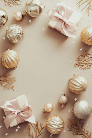 Christmas composition. Frame made of golden balls and gift boxes on pastel beige background. Flat lay, top view.
