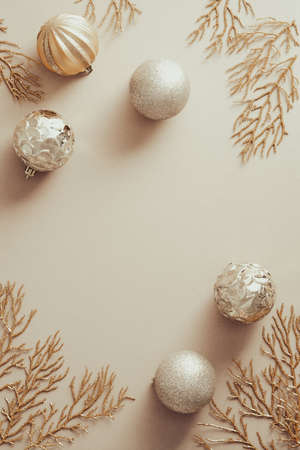 Christmas golden decorations on pastel beige background, flat lay.