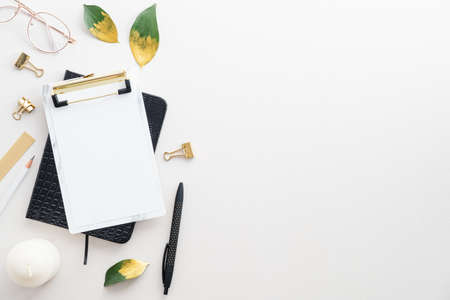 Top view paper clipboard, notebook, office stationery on white desk table. Elegant feminine workspace.