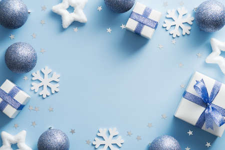 Modern Christmas background with stylish decorations, gift boxes, stars, balls on blue. Flat lay, top view, copy space.
