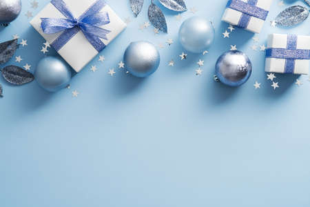 Christmas frame made of gift boxes, silver balls, confetti on blue background. Flat lay, top view, copy space.