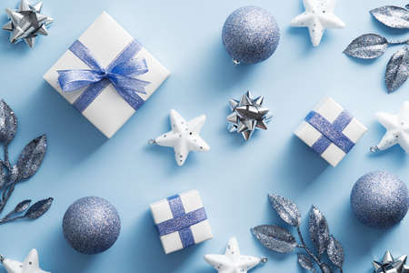 Christmas flat lay composition with gift boxes, balls, branches on blue background. Top view, flat lay.