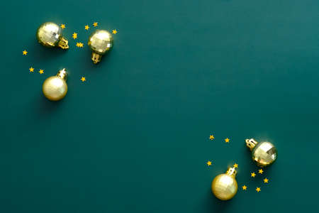 Christmas golden balls and confetti on green table. Christmas flyer design, New Year greeting card mockup.