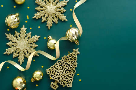 Luxury Gold Christmas decorations on green background. Flat lay, top view, copy space.