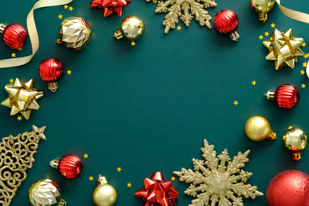 Elegant Christmas frame made of golden and red decorations on green background. Flat lay, top view, copy space. Xmas banner design, Happy New Year greeting card template.